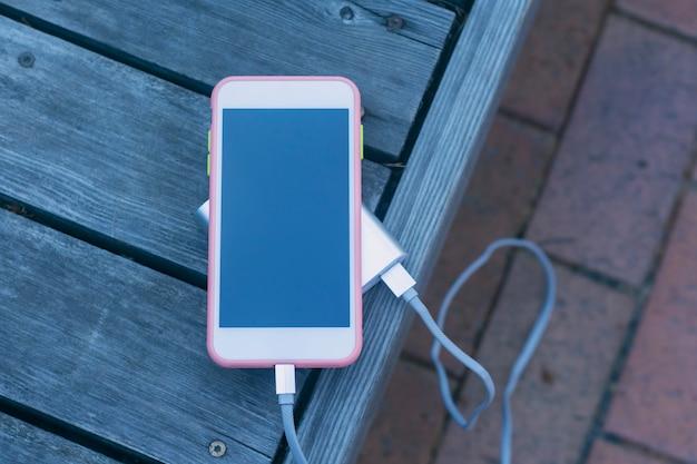 ポータブル充電器は、木製のベンチでスマートフォンを充電します。暗い画面とパワーバンクを備えた携帯電話のモックアップ。