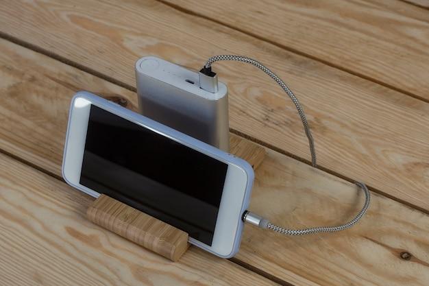 ポータブル充電器は、木製のテーブルでスマートフォンを充電します。暗い画面とパワーバンクを備えた携帯電話のモックアップ。