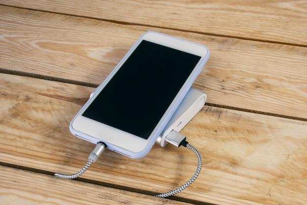 휴대용 충전기는 나무 테이블에 스마트폰을 충전합니다. 어두운 화면과 전원 은행이 있는 휴대폰 모형.