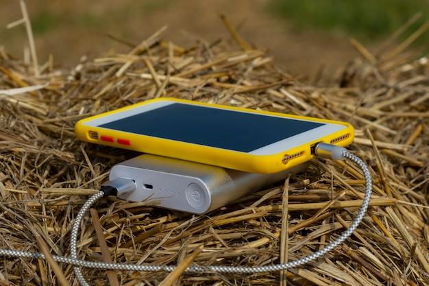휴대용 충전기는 야외에서 건초를 배경으로 스마트폰을 충전합니다.