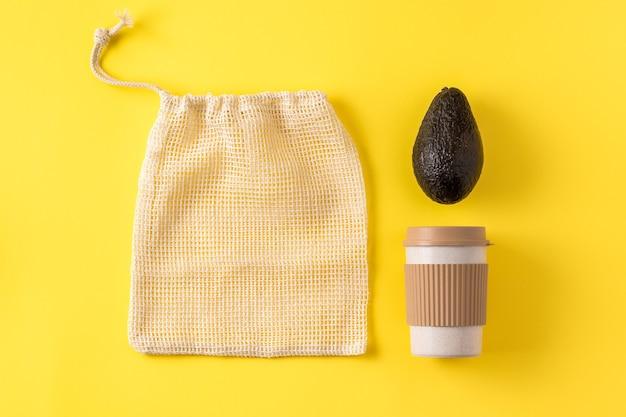 Portable eco cup, produce bag, avocado on yellow surface.