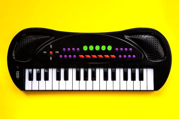 Portable electronic keyboard on yellow background . toy synthesizer.