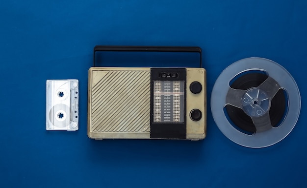 Portable radio receiver, audio cassette and magnetic tape reel on classic blue