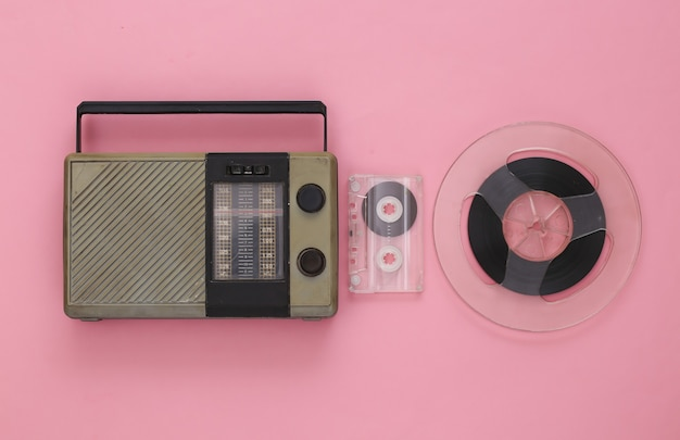 Portable radio receiver, audio cassette and magnetic tape reel on pink