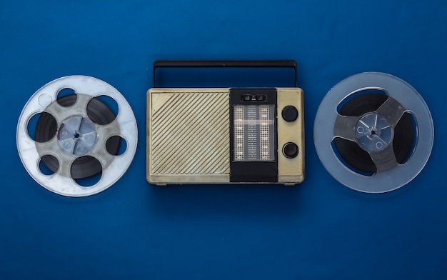 Portable radio receiver and audio magnetic tape reel on classic blue
