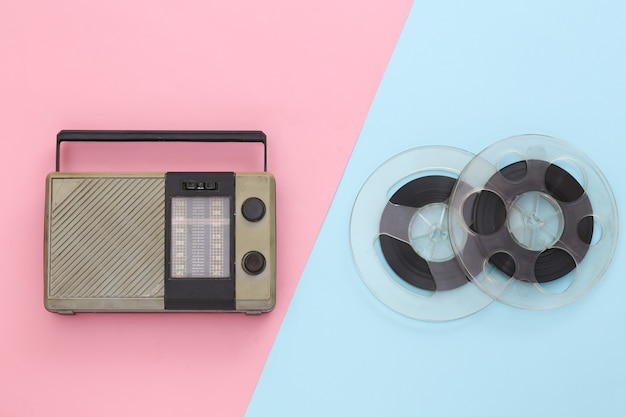 Portable radio receiver and audio magnetic tape reel on pink blue pastel