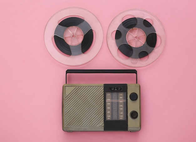 Portable radio receiver and audio magnetic tape reel on pink