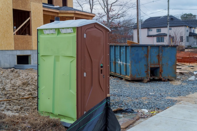 Portable restroom on a dumpsters being full with garbage new house under construction.