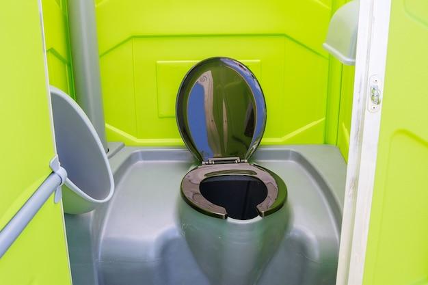 열린 문으로 구름의 배경에 대해 잔디에 휴대용 화장실 모바일 화장실