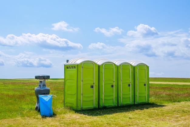 구름의 배경에 잔디에 휴대용 화장실. 이동식 화장실.