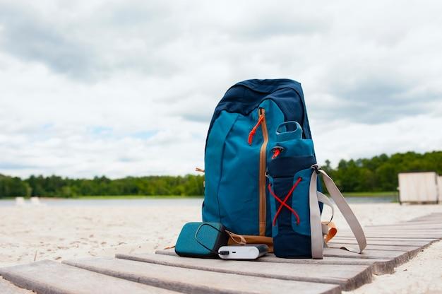 휴대용 여행용 충전기. power bank는 여행용 가방을 배경으로 음악 블루투스 스피커를 충전합니다.