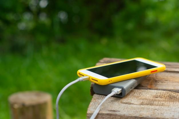 휴대용 여행용 충전기. power bank는 자연을 배경으로 나무 테이블에 스마트폰을 충전합니다. 관광을 주제로 한 개념입니다.