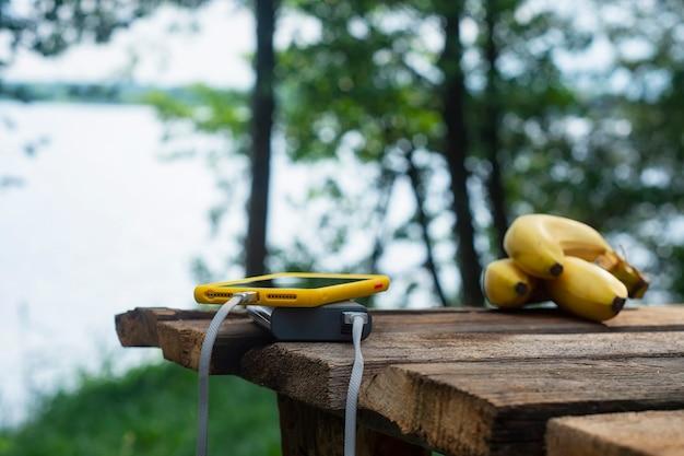 휴대용 여행용 충전기. power bank는 자연을 배경으로 바나나가 있는 나무 테이블에 스마트폰을 충전합니다. 관광을 주제로 한 개념입니다.