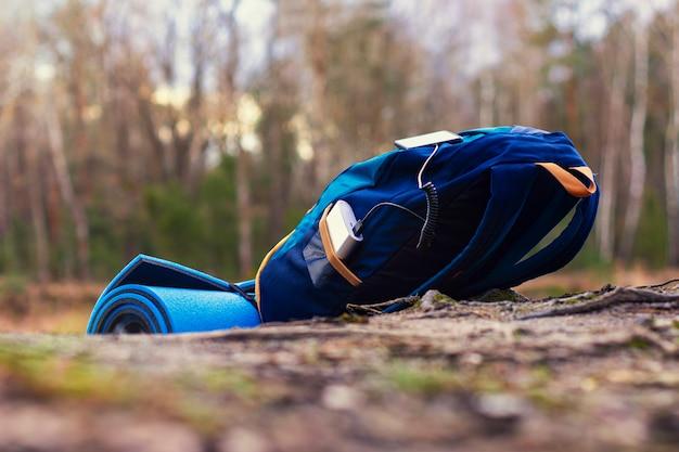 휴대용 여행용 충전기. power bank는 여행 가방과 숲을 배경으로 스마트 폰을 충전합니다. 관광 주제에 대한 개념.
