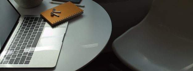 Portable workspace with  laptop, stationery and supplies on white circle table