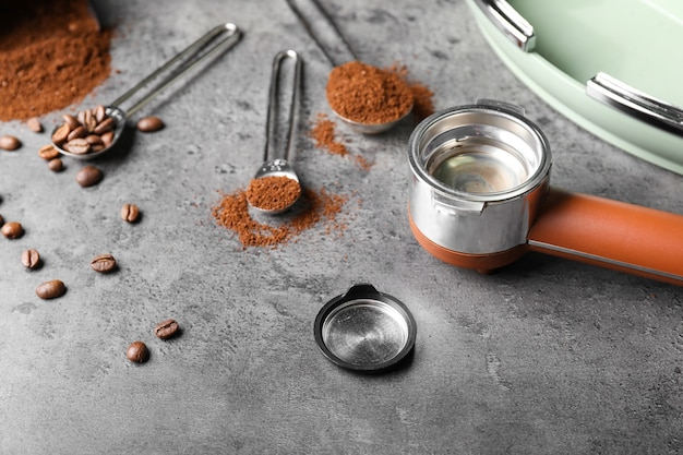 Portafilter with coffee powder and beans on grey