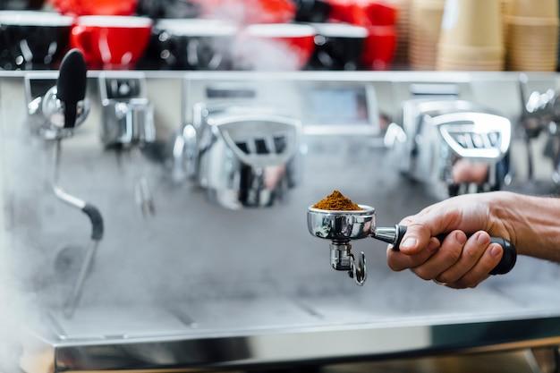 Деталь рука человека, держащего portafilter получателя заполнены кофейной гущи во время приготовления эспрессо