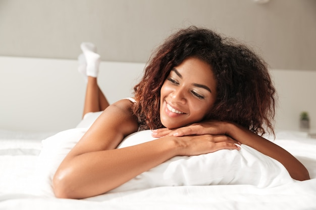 Portait of african cheerful lady in bed with pillow