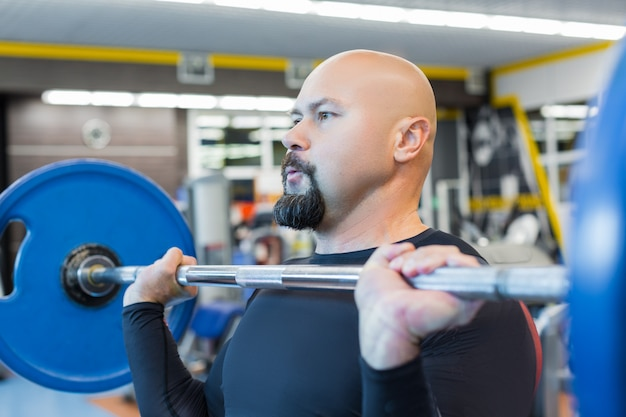 Portait of a brutal middle aged man lifting a barbell in gym.