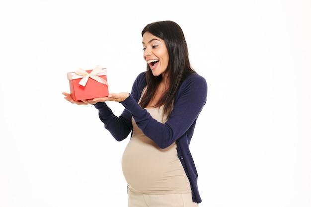 Ritratto di un allegro felice donna incinta con confezione regalo