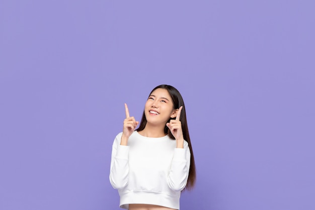 Portait of cute smiling young asian woman pointing hands up and looking at copyspace above in purple isolated wall