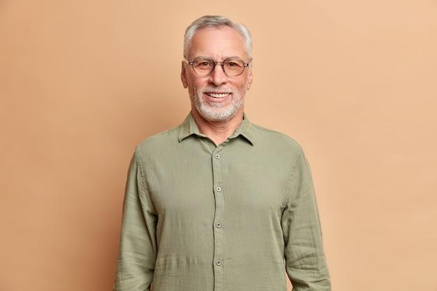 Ritratto di bell'uomo anziano europeo sorride positivamente gode della pensione indossa camicia e occhiali ha denti bianchi perfetti isolati sopra il muro beige dello studio