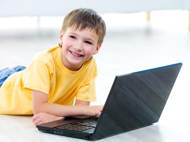 Ritratto di giovane ragazzo sorridente felice con il computer portatile sul pavimento - al chiuso