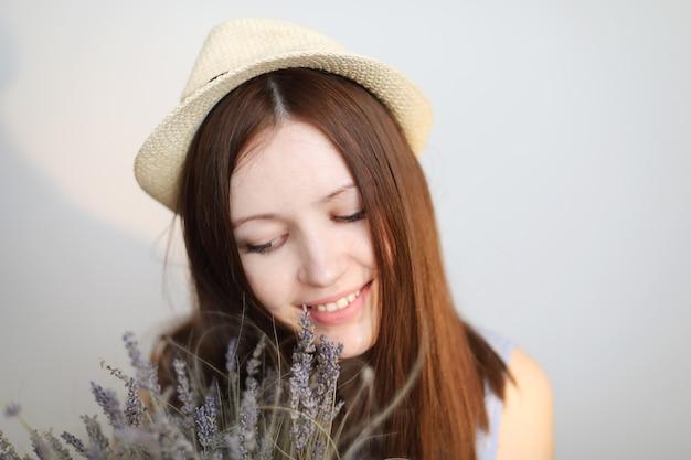 Портрет красивой молодой женщины в летней шляпе с цветами лаванды в руках