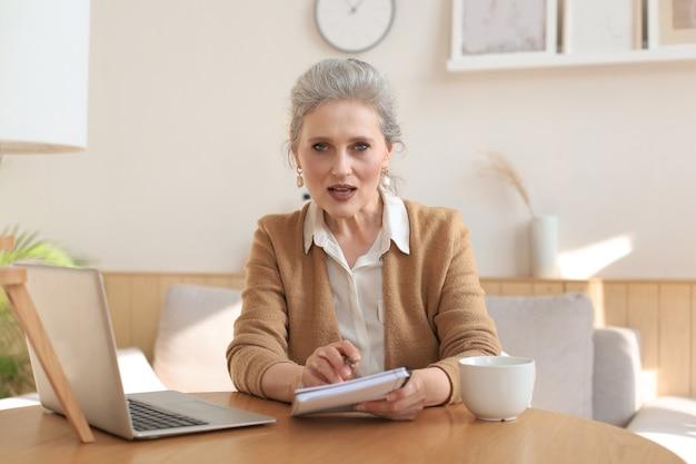 카메라를 보고, 화상 통화, 면접 또는 온라인 데이트를 하는 아름다운 중년 여성의 초상화.