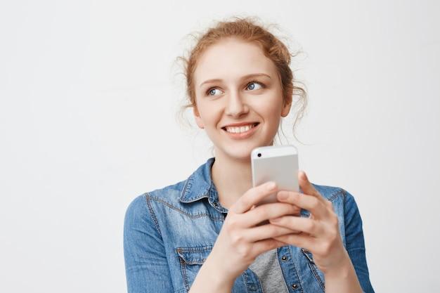 厄介な髪のかわいい柔らかい赤毛の10代の少女の肖像、よそ見、スマートフォンを押しながら笑顔
