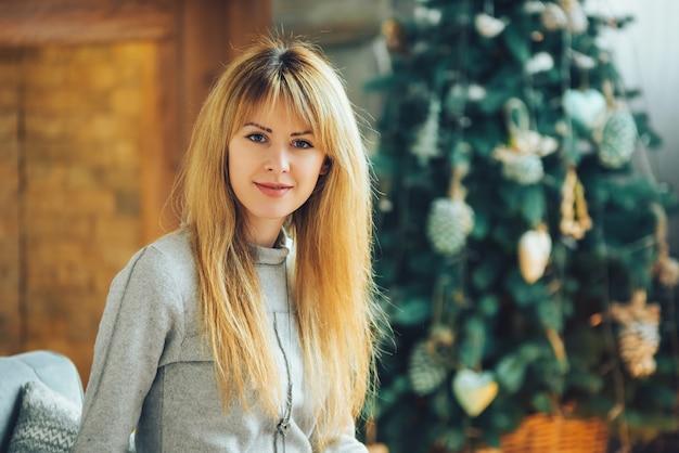 Портрет красивой блондинки на фоне новогоднего украшения