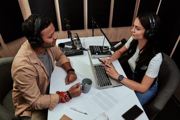 ライブをモデレートしながらさまざまなトピックについて話し合う2人のラジオホストの若い男性と女性の肖像