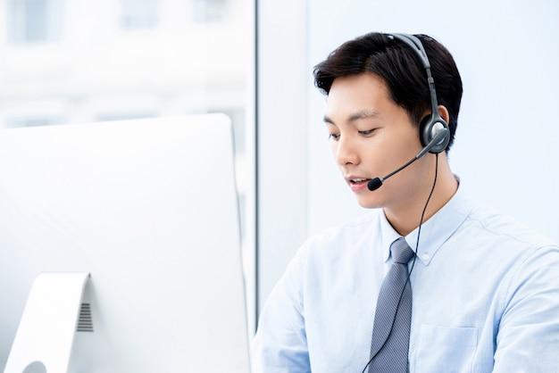 Портрет молодого красивого мужского азиатского агента центра телефонного обслуживания смотря компьютер работая в офисе