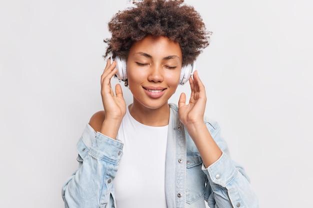 Il ritratto di una donna afroamericana soddisfatta gode di un buon suono e la canzone preferita tiene le mani sulle cuffie stereo wireless utilizza la migliore app di musica gratuita indossa una maglietta bianca e una camicia di jeans posa al coperto