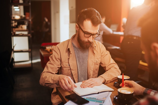 A portait of serious businessman sitting in front of his partner in small and cozy cafe. he is studying information that is in document. he is preparing for meeting.