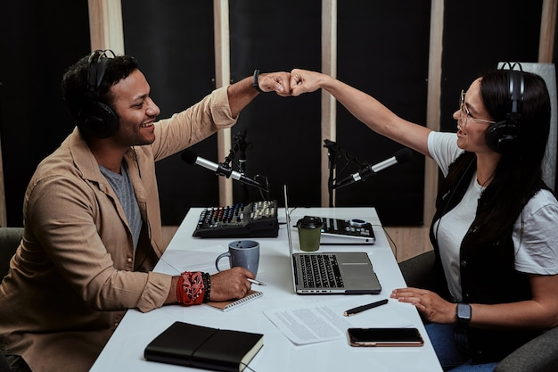 Portait of two cheerful radio hosts young man and woman fist bump while talking moderating a live