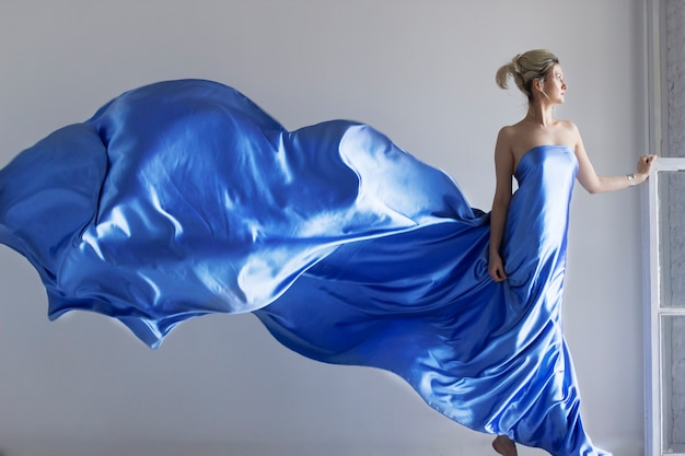 Portait of young adult beautiful woman in fashionable silk dress