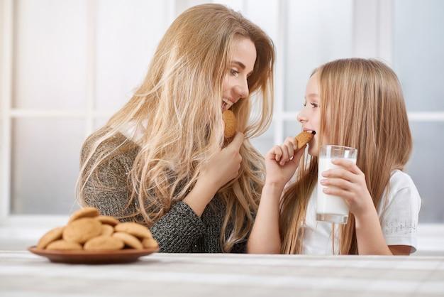 Portarait старших и младших сестер едят печенье и улыбаться