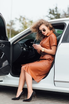 Portarit of businesswoman holding phone in the car