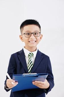 Portarit of joyful smiling vietnamese kid in formalwear with folder writing in document