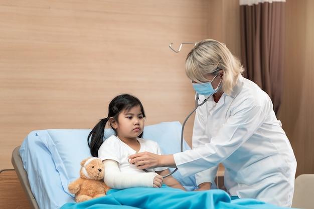 Smaile医師の小児科医とテディベアとベッドの上の小さな女の子の患者のportarit
