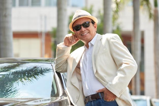 Porteait of asian man leaning on car