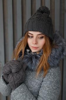 나무 벽에 빈티지 장갑에 모피와 회색 겨울 코트에 니트 모자에 매력적인 귀여운 젊은 여자의 포터. 슬라브 외모의 아름다운 소녀.