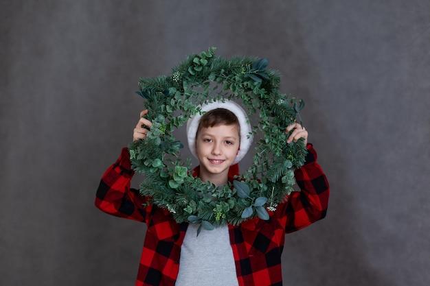 クリスマスリースと赤い格子縞のシャツを着た笑顔の子供のポーター。新年と幸せな休日