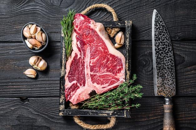 Сырая говядина porterhouse или t bone стейк с зеленью и солью на деревянном подносе.