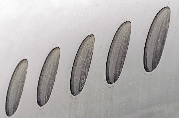 Porthole windows of an airplane wet weather in rain drops of water, close-up.