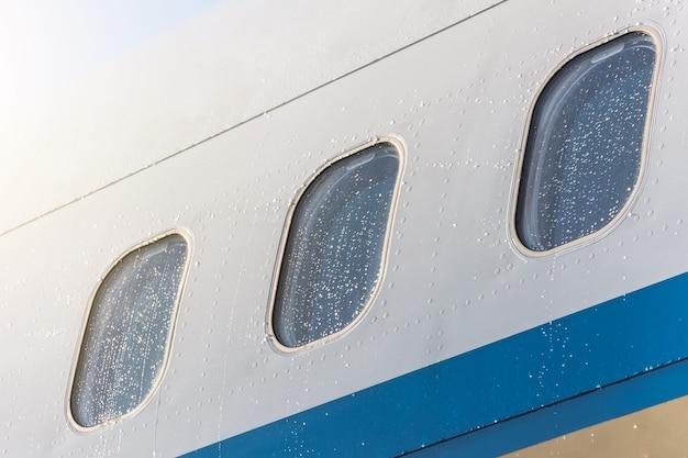 雨滴の水の中の飛行機の舷窓の窓がクローズアップ