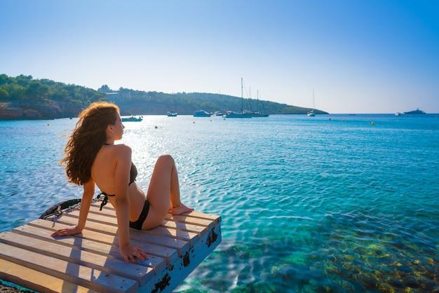 イビサビキニの女の子はportinatxビーチでリラックス