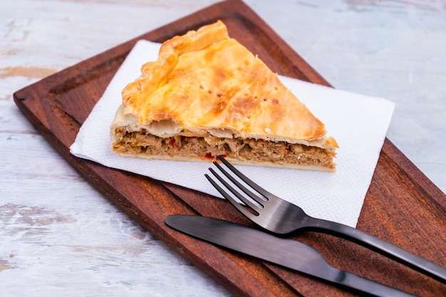 Portioin of empanada gallega, traditional plant of galician cuisine, in spain, tart with tuna and vegetables. traditional cuisine.