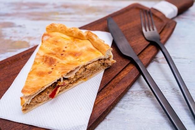 Портиоин из empanada gallega, традиционное растение галисийской кухни, в испании, тарт с тунцом и овощами. традиционная кухня.